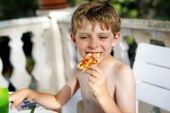 Den gulliga sunda förskole- ungepojken äter nytt pizzasammanträde på terrass i sommar, utomhus Royaltyfria Foton