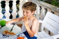 Den gulliga sunda förskole- ungepojken äter nytt pizzasammanträde på terrass i sommar, utomhus Arkivbild