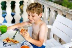 Den gulliga sunda förskole- ungepojken äter nytt pizzasammanträde på terrass i sommar, utomhus Arkivfoto
