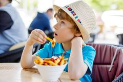 Den gulliga sunda förskole- ungepojken äter potatisar för franska småfiskar med ketchup Royaltyfri Foto