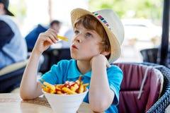 Den gulliga sunda förskole- ungepojken äter potatisar för franska småfiskar med ketchup Fotografering för Bildbyråer