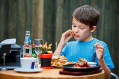 Den gulliga sunda tonåringpojken äter hamburgaren och potatisen Arkivbilder