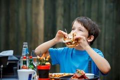 Den gulliga sunda tonåringpojken äter hamburgaren och potatisen Arkivfoto
