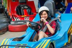 Den gulliga thailändska flickan kör går-kart från startpunkten arkivbild