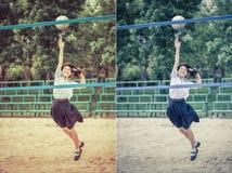 Den gulliga thailändska skolflickan spelar strandvolleyboll i skolaunifo arkivfoto