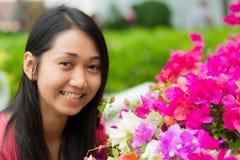 Den gulliga thailändska flickan är jätteglad med blommor Fotografering för Bildbyråer