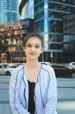 Den gulliga tonåriga flickan i omslag står på gatan mot en modern skyskrapa royaltyfri bild