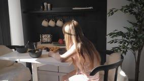 Den gulliga tonårs- flickan sitter på matställetabellen och ätahavregröt för sunt livsstilbegrepp för frukost lager videofilmer