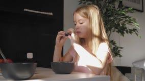 Den gulliga ton?rs- flickan sitter p? matst?lletabellen och ?tahavregr?t f?r sunt livsstilbegrepp f?r frukost lager videofilmer