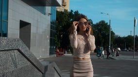 Den gulliga unga affärsflickan i trendig klänning och solglasögon går och talar vid mobiltelefonen lager videofilmer