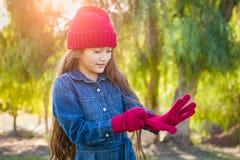 Den gulliga unga flickan för det blandade loppet sätter på den röda toppluvan och handskar arkivfoto