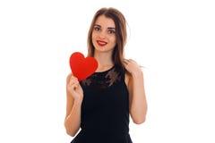 Den gulliga unga flickan med röd läppstift och den svarta klänningen ser raka leenden och rymmer valentin Arkivfoton