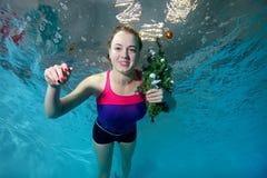 Den gulliga unga flickan simmar undervattens- i pölen på en blå bakgrund med en julgran med en leksak i hand Royaltyfri Fotografi