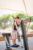 Den gulliga unga flickan som övar armar, och bröstkorgen på arg instruktöridrottshall bearbetar med maskin utomhus Royaltyfri Fotografi