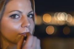 Den gulliga unga flickan som sätter på läppstift, natten tänder bokeh Royaltyfri Foto