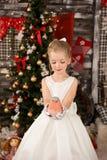 Den gulliga unga härliga flickan bär julklänningen Arkivfoto