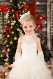 Den gulliga unga härliga flickan i vit jul klär Fotografering för Bildbyråer