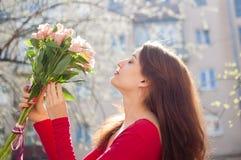 Den gulliga unga kvinnan har mottagit en stor bukett av färgrika blommor, och hon ser precis den som spenderar tidyttersidan royaltyfri bild