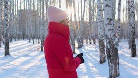 Den gulliga unga kvinnan i rött vinteromslag står i bildmässig stad parkerar med björkar på frostig solig dag och frysningar i fö stock video