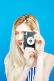 Den gulliga unga kvinnan i sommar gjord randig klänning använder den Retro kameran på blå bakgrund i studio Arkivbild