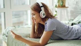 Den gulliga unga kvinnan lyssnar till musik i hörlurar och rörande smartphoneskärm som hemma vilar på säng teknologi lager videofilmer