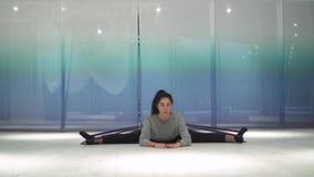 Den gulliga unga kvinnan som gör sträckning genom att använda konditiongummi och, vippar på kroppen i olika sidor på mattt i idro arkivfilmer