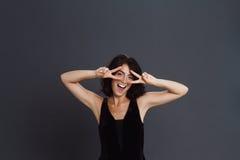 Den gulliga unga kvinnan som poserar över grå bakgrund och, gör två fred den roliga gesten fotografering för bildbyråer