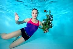 Den gulliga unga lagledare-flickan simmar undervattens- i pölen med leksaken i hans hand och att se kameran Arkivbilder