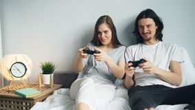 Den gulliga unga den parpojkvännen och flickvännen spelar videogamen på säng hemma stock video