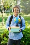 Den gulliga unga pojken i runda exponeringsglas och den blåa skjortan rymmer böcker med hans händer i parkerar Läsa och lära begr royaltyfri foto