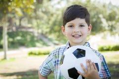 Den gulliga unga pojken som spelar med fotbollbollen parkerar in Arkivfoto