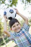 Den gulliga unga pojken som spelar med fotbollbollen parkerar in Royaltyfri Foto