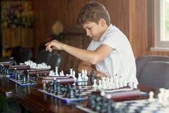 Den gulliga unga pojken spelar schack med träschackbrädet Schackturnering, kurs, läger, utbildning arkivbild