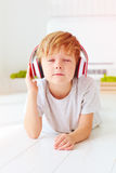 Den gulliga ungen lyssnar till musiken som hemma kopplar av Arkivbild