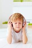 Den gulliga ungen lyssnar till musiken som hemma kopplar av Arkivfoton