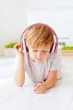 Den gulliga ungen lyssnar till musiken som hemma kopplar av Royaltyfria Bilder