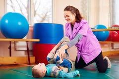 Den gulliga ungen med handikapp har musculoskeletal terapi, genom att göra övningar i kroppfixandebälten royaltyfria bilder