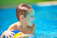 Den gulliga ungen som spelar i vattensport, spelar i pöl Royaltyfri Foto