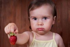 Den gulliga upprivna lilla flickan rymmer den stora mogna jordgubben Royaltyfri Foto