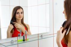 Den gulliga varma flickan ser i spegeln och kammar hennes hår Fotografering för Bildbyråer