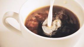 Den hällande strömmen mjölkar in i en kopp kaffe stock video