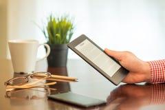 In den Händen einen modernen ebook Leser und Papierbücher halten lizenzfreies stockfoto