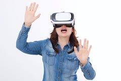 Den häpna caucasian kvinnan som ser i en VR, rullar med ögonen och gör en gest vid händer som isoleras på vit bakgrund Virtuell v arkivfoton