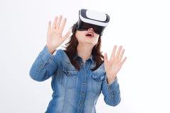 Den häpna caucasian kvinnan som ser i en VR, rullar med ögonen och gör en gest vid händer som isoleras på vit bakgrund Virtuell v royaltyfria foton