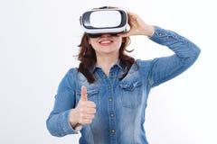 Den häpna caucasian kvinnan som ser i en VR, rullar med ögonen med den stora tummen som isoleras upp på vit bakgrund Virtuell ver arkivfoto