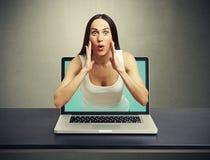 Den häpna kvinnan fick ut ur bärbara datorn Arkivbild