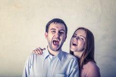 Den häpna mellan skilda raser unga nätta kvinnlign och manliga öppna mouthes brett, utropar med förvirring, reagerar på plötslig  royaltyfri bild