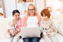 Den härliga äldre farmodern ser bärbara datorn med hennes lilla barnbarn royaltyfria bilder