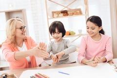 Den härliga äldre kvinnan undervisar barn att dra Barnattraktion med målarfärger royaltyfri bild