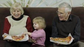 Den härliga äldre mannen och kvinnan äter pizza med deras sondotter arkivfilmer